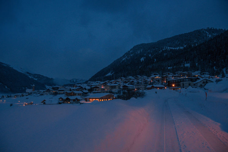 Houses By Mountains Against Sky At Night During Winter