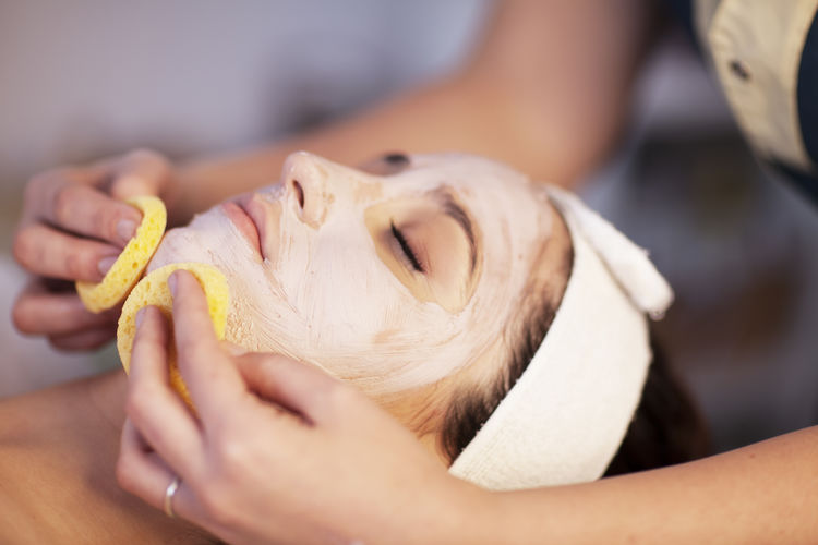Close Up Of Therapist Applying Facial Mask At Therapy