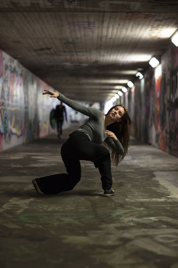 Full length of woman doing stunt in tunnel