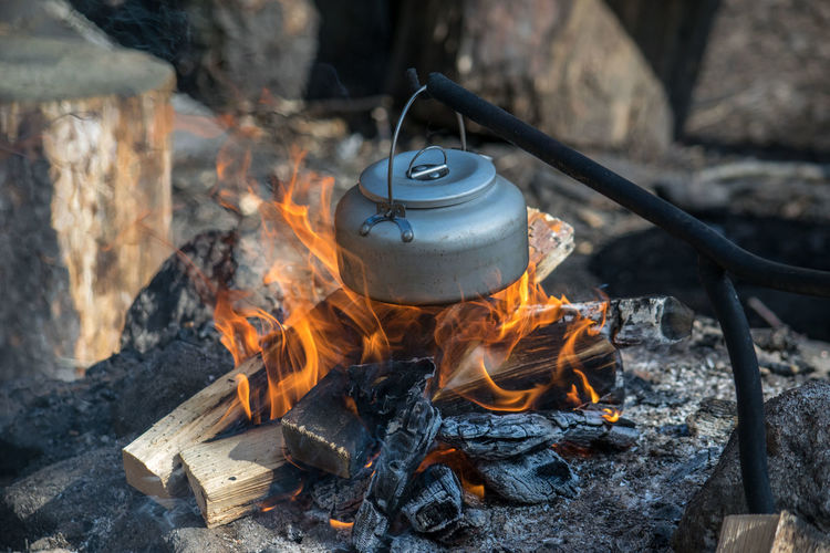 Kettle hanging over campfire