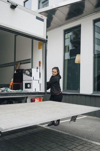 Portrait of woman standing against building