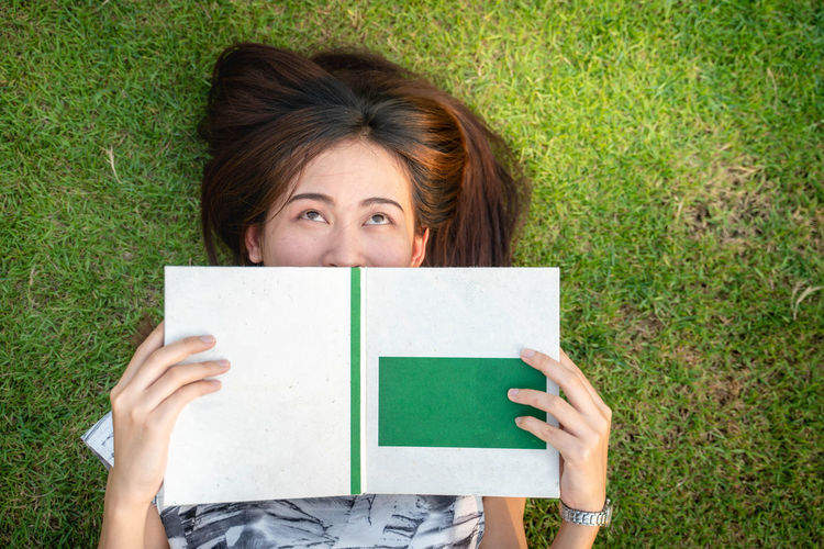 One Person Portrait Looking At Camera Front View Holding Adult Grass Lying Down Publication Leisure Activity Headshot Real People Young Adult Book Brown Hair Women Green Color Plant Obscured Face
