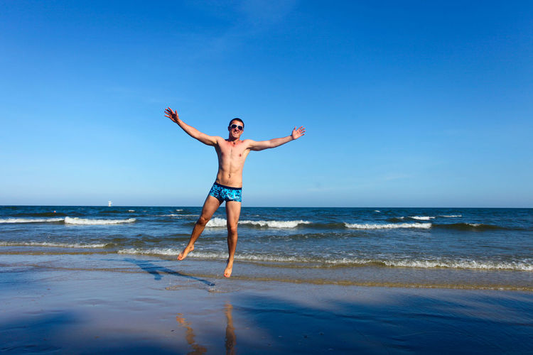 Full Length Portrait Of Shirtless Man With Arms Outstretched Jumping At Beach Against Sky