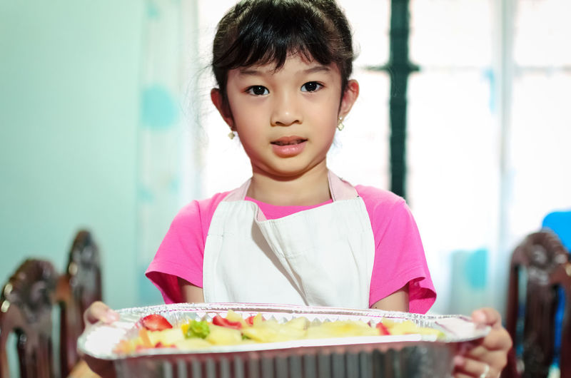 Portrait of cute girl holding food in tray at home