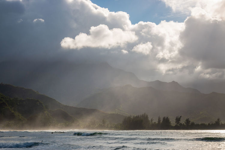 Sceniv view of sea and mountains at waioli beach park, hanalei bay, kauai, hawaii, usa against sky