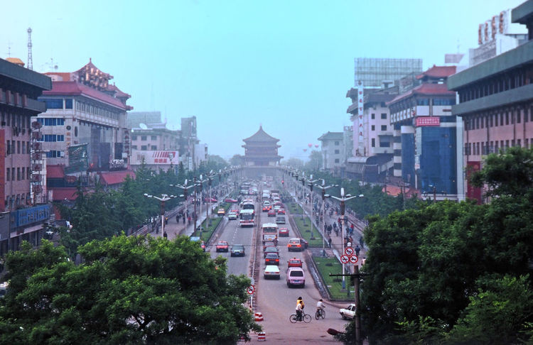 The main road in the city of Xi'an, with the Drum Tower at the end of the street - Xi'an, China Street Architecture People City Urban Tree Outdoors Cityscape Clear Sky Main Road Avenue Of Trees Drum Tower Xi'an China City Street Scene Chinese Cars Chinese Hotels