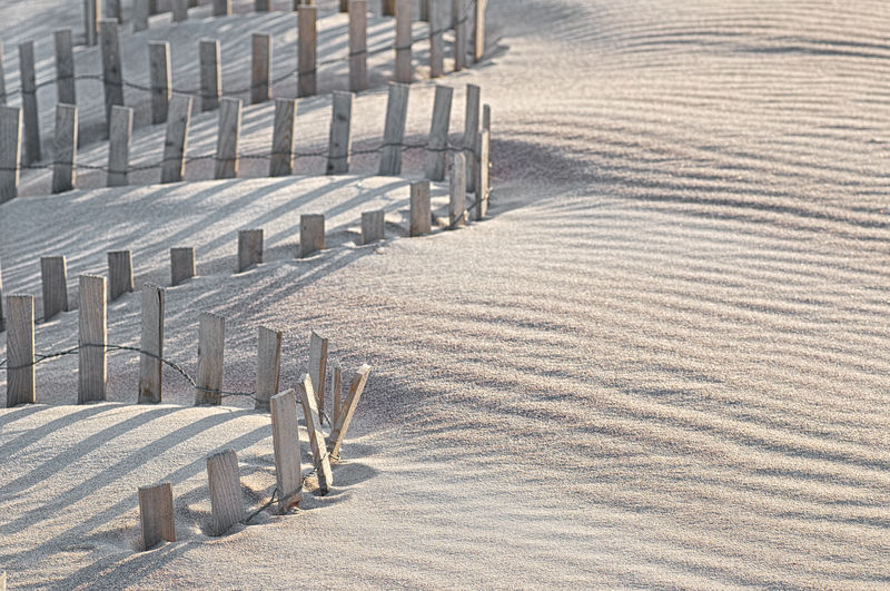 High angle view of wooden fence at sandy beach