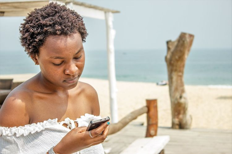 Close-Up Of Woman Holding Smart Phone At Beach Against Sky