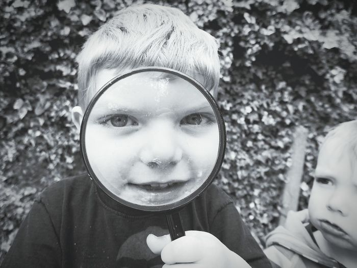 Portrait of boy looking through magnifying glass while standing with sibling