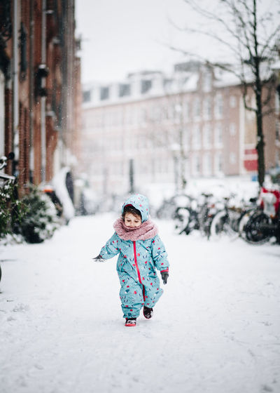 Cute girl walking on snowy field in city