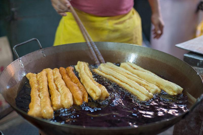 Midsection of man preparing food in cooking utensil