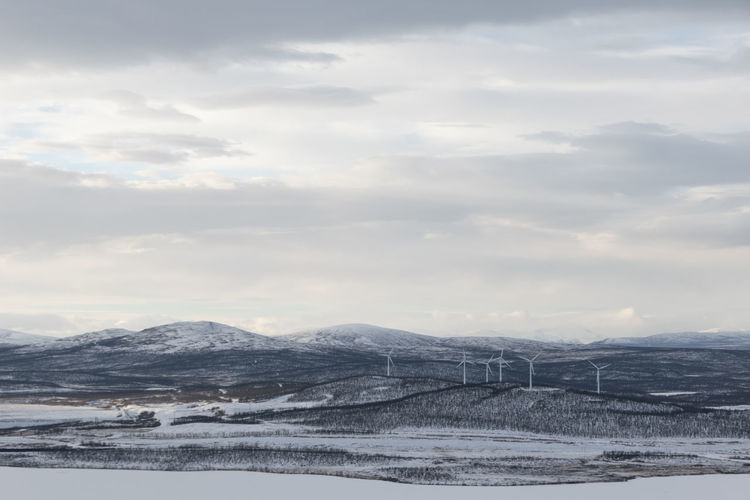 Scenic view of snow covered land with wind turbines against sky.