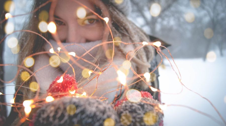 Portrait of young woman with illuminated string lights during winter
