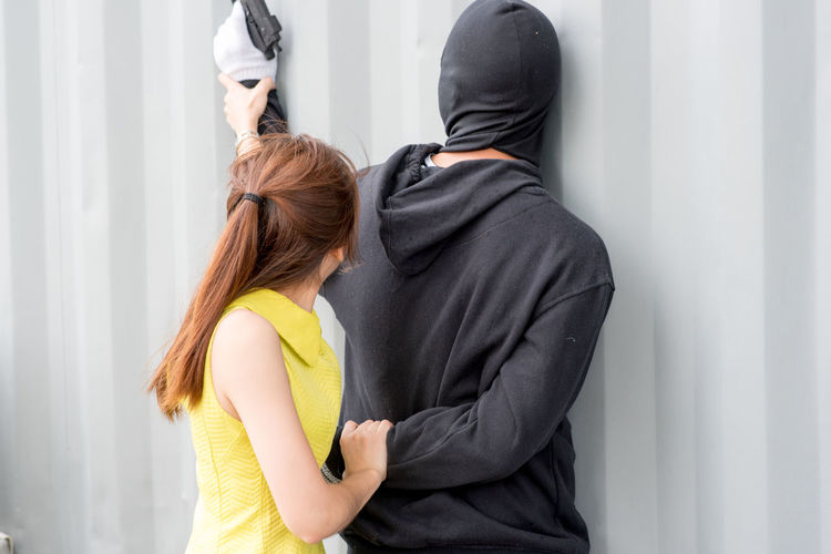 Young woman defending herself from burglar against wall