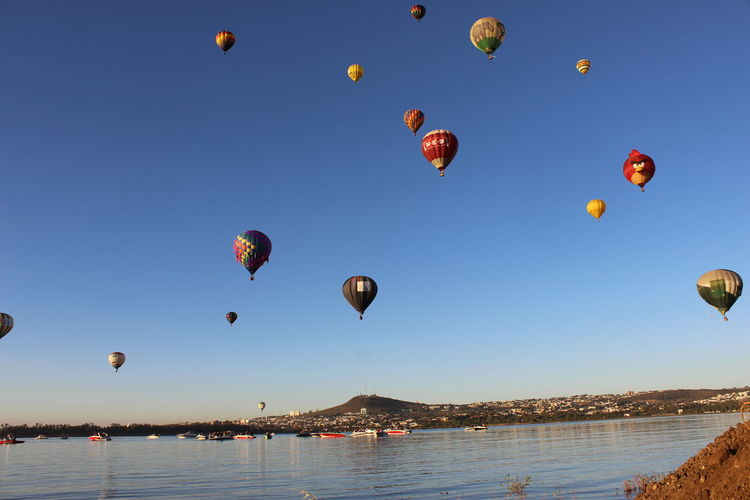 Hot air balloons flying over lake against clear sky