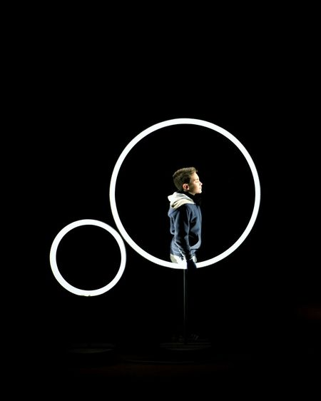Boy with illuminated plastic hoop standing against black background