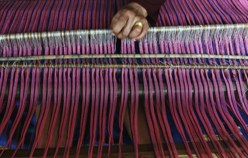 Cropped image of worker working on loom in textile factory