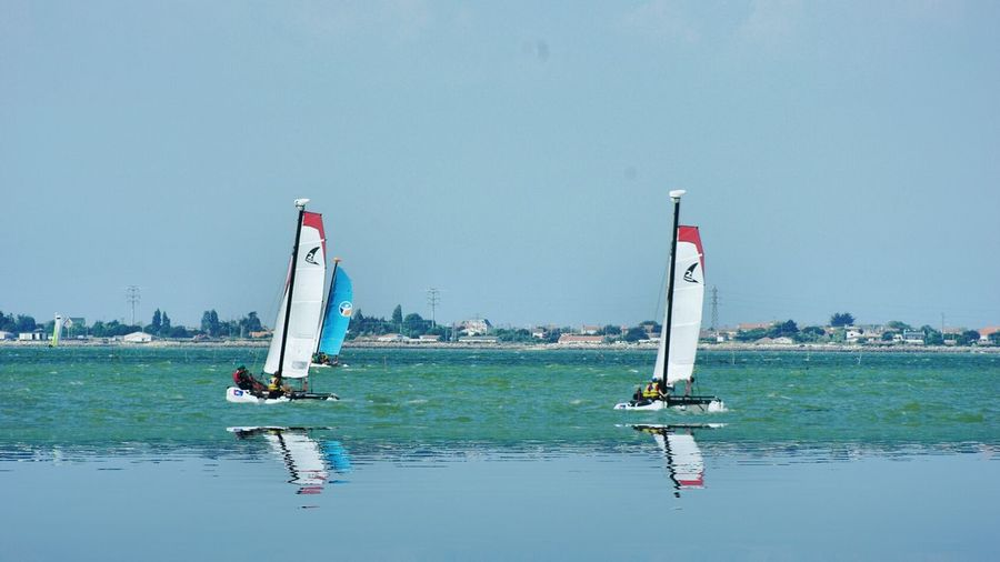Sailboat Racing In Sea Against Clear Blue Sky