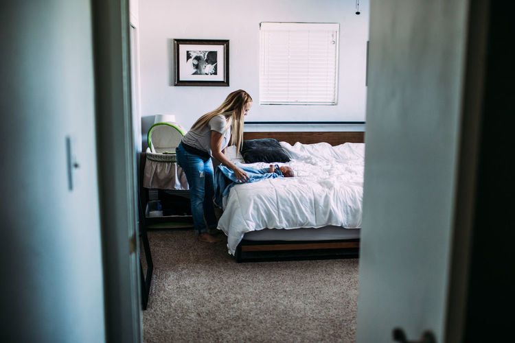 Woman sitting on bed in bedroom