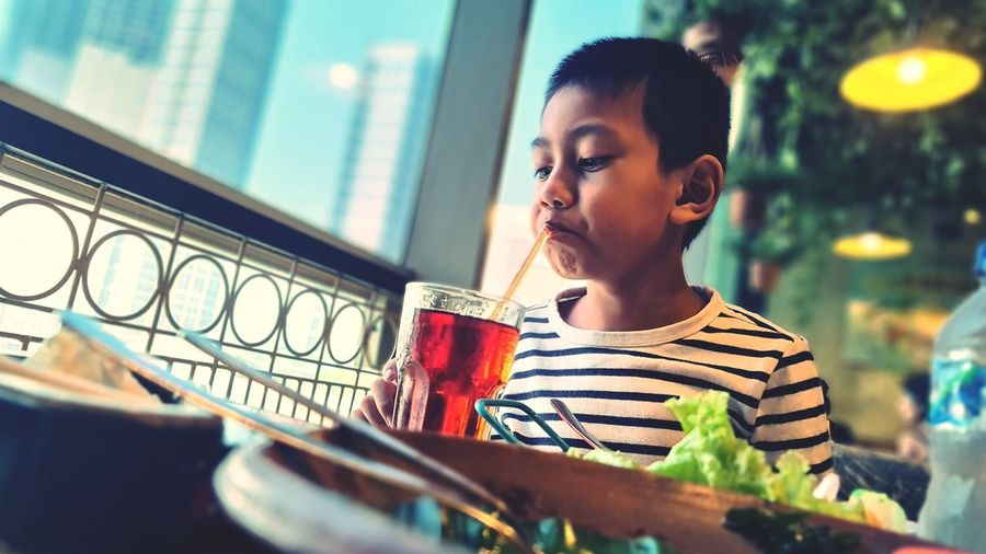 Boy drinking ice tea in cafe