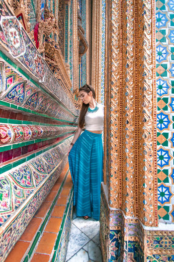 Beautiful woman standing in mosaic building