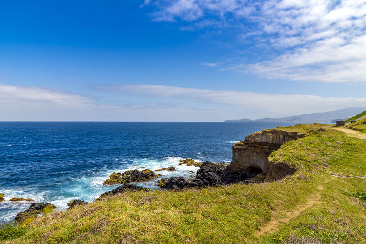 Scenic View Of Sea And Cliff Against Blue Sky