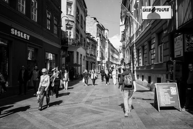 People walking on city street amidst buildings