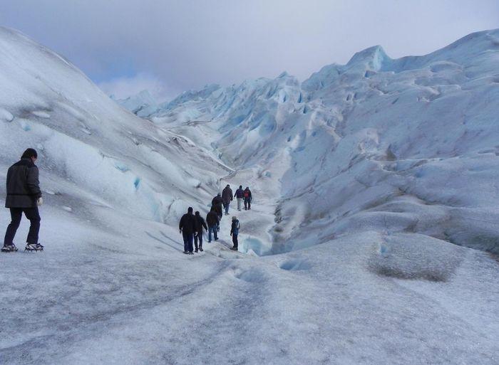 Rear view of people hiking at moreno glacier