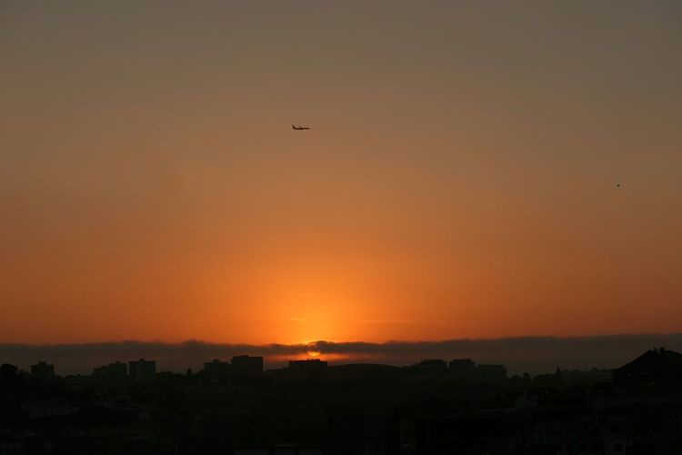 Silhouette airplane against orange sky during sunset