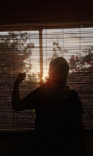Teenage Girl Standing Against Window Blinds During Sunset