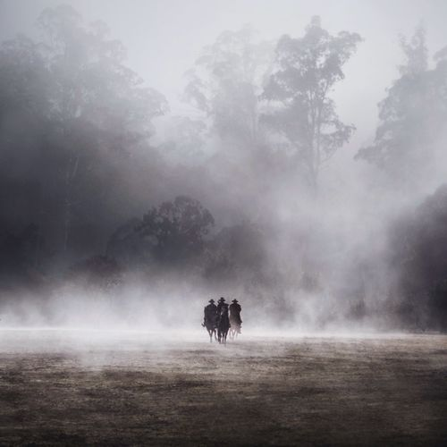 THREE MEN HORSEBACK RIDING IN THE FOG