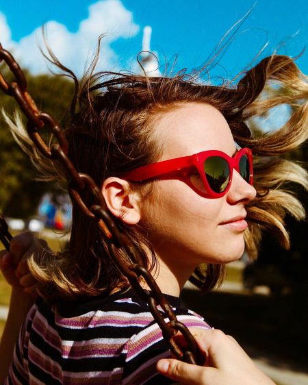 Close-up of woman wearing sunglasses while swinging during sunny day