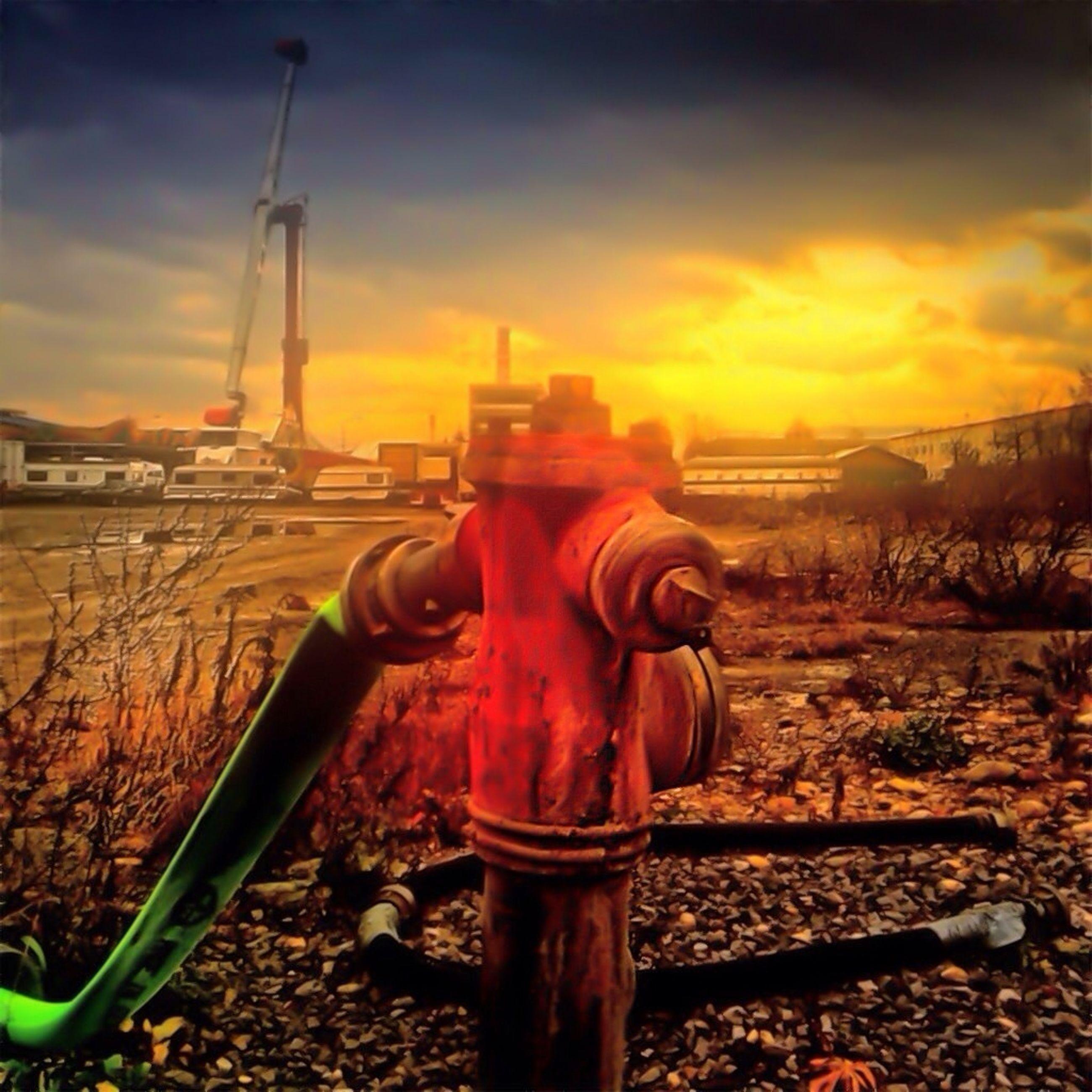sunset, sky, orange color, railroad track, cloud - sky, industry, metal, built structure, outdoors, sunlight, nature, landscape, building exterior, field, cloud, no people, architecture, metallic, tranquility, factory