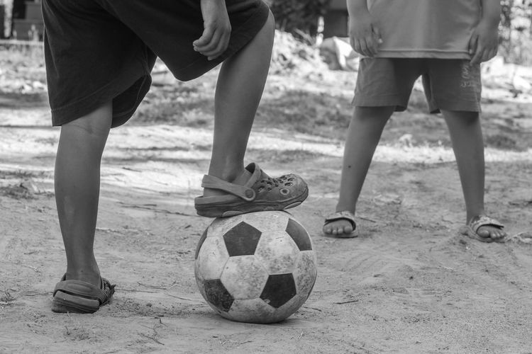 Low section of boys playing with soccer ball