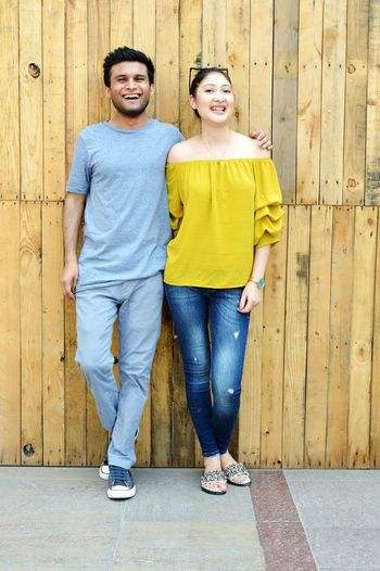 Portrait of cheerful young couple standing against wall