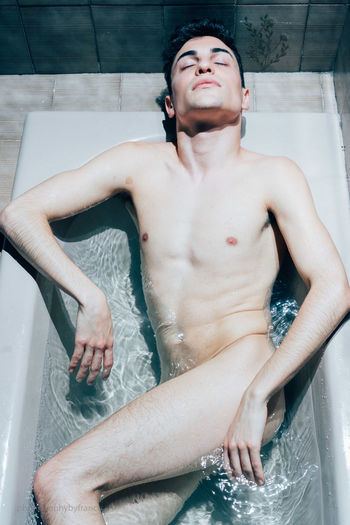 Midsection of shirtless man in bathroom