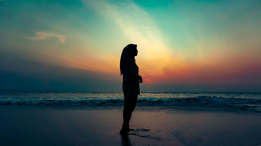 Silhouette woman standing on beach against sky during sunset