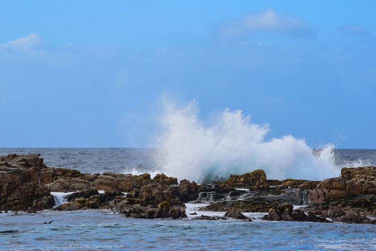 Water splashing on rocks by sea against sky