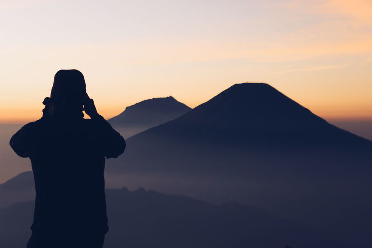 Silhouette man photographing mountains against sky during sunset