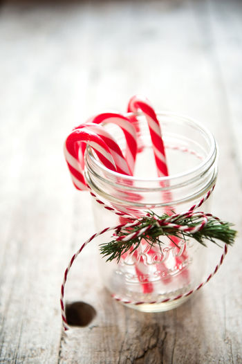 Candy canes in glass container on wooden table