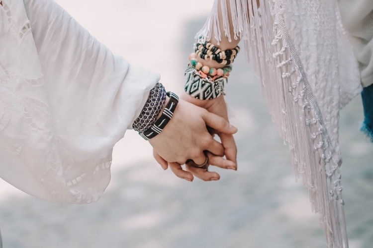Hippies holding hands with boho beaded jewelry. summer freedom and friendship concept