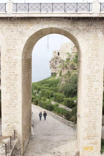 Rear View Of Man And Woman Walking On Footpath Seen Through Arch
