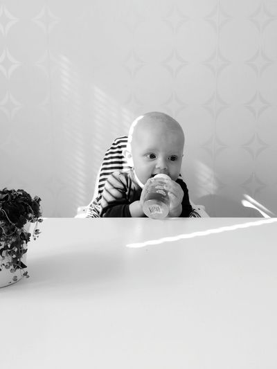 Cute baby drinking from bottle at home
