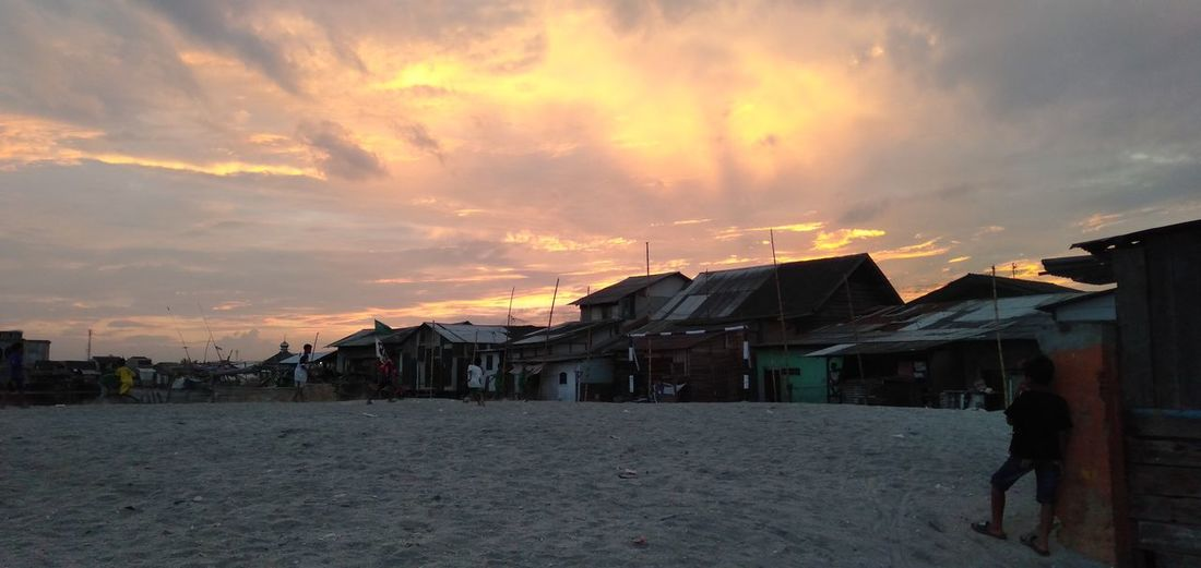 Houses on beach by buildings against sky during sunset