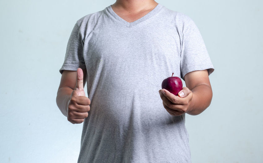 Midsection of man holding apple against white background