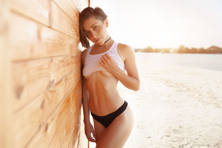 Portrait of sensuous young woman touching breast while standing by wooden wall