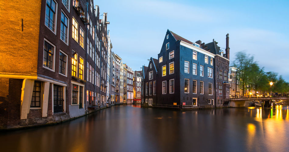 Canal Amidst Illuminated Buildings In City Against Sky