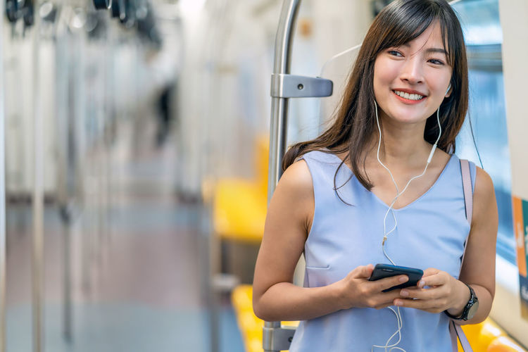 Portrait of smiling young woman using mobile phone while standing on bus