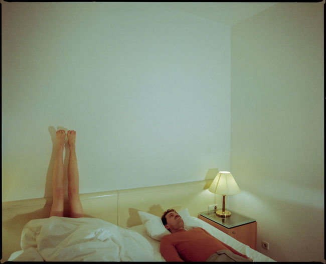 People relaxing on bed against wall at home