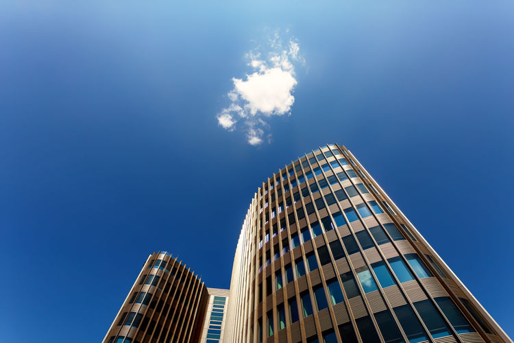 Modern building with round architectural style and windows reflecting the sky